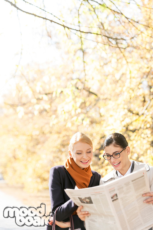 Happy businesswomen reading newspaper together at park