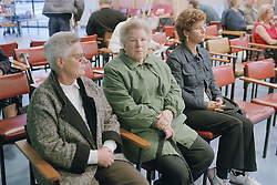 Three women sitting in waiting room of Fracture Clinic in hospital,