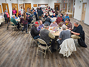 """26 FEBRUARY 2020 - FARMINGTON, MINNESOTA: The community dinner at Faith Church, a United Methodist Church in Farmington, MN, about 30 minutes south of the Twin Cities. The dinner is sponsored by Loaves & Fishes, a Christian organization that provides food for community dinners and foodbanks. Farmington, with a population of 21,000, is a farming community that has become a Twin Cities suburb. The city lost its only grocery store, a Family Fresh Market, in December, 2019. The closing turned the town into a """"food desert."""" In January, Faith Church started serving the weekly meals as a response to the store's closing. About 125 people per week attend the meal at the church, which is just a few blocks from the closed grocery store. The USDA defines food deserts as having at least 33% or 500 people of a census tract's population in an urban area living 1 mile from a large grocery store or supermarket. Grocery chains Hy-Vee and Aldi both own land in Farmington but they have not said when they plan to build or open stores in the town.      PHOTO BY JACK KURTZ"""