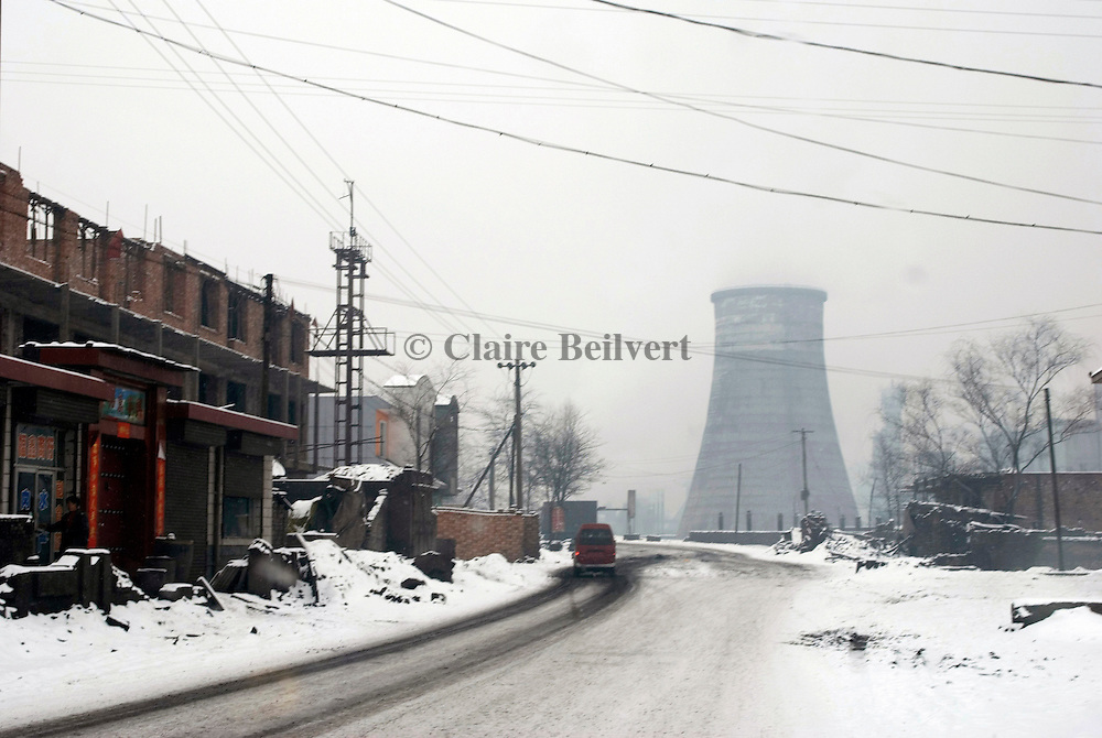 Tower of a coal power plant near a village. Shanxi Province is China's largest coal supplier: 500 millions of tonnes per year. This Province is also the most polluted of China. More than 60 percent of the province 's surface water cannot be used due to pollution and the air is hardly breathable.