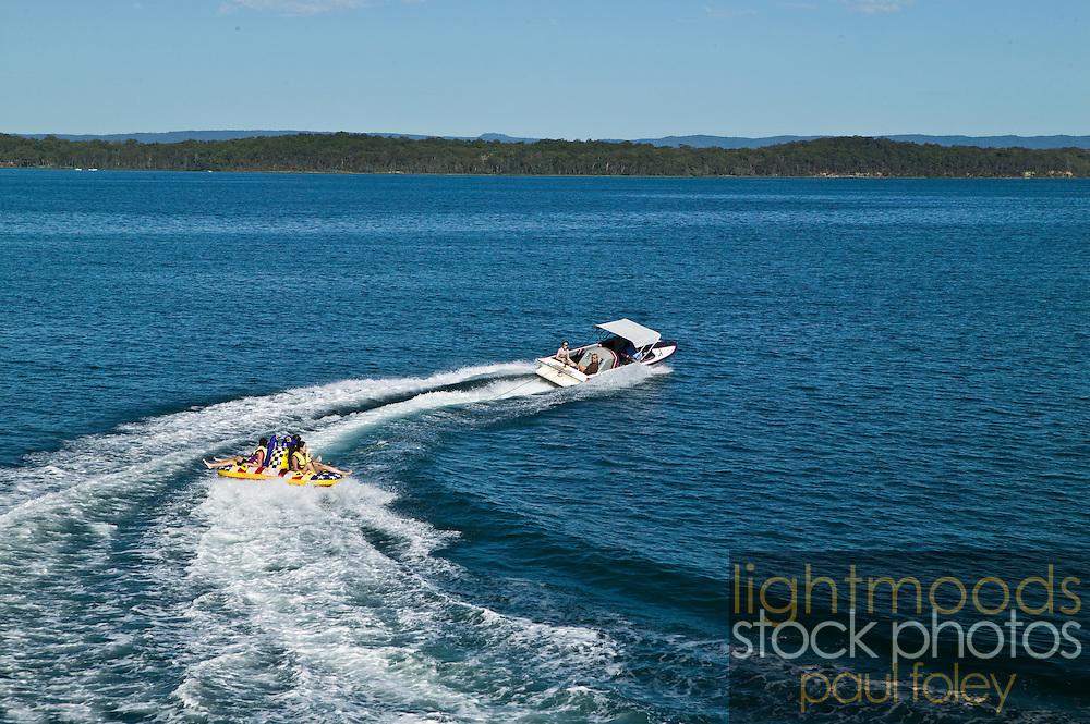 Teenagers being towed behind a speedboat on Lake Macquarie, East Coast Australia