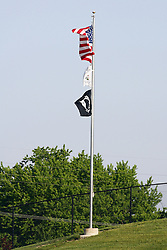 18 May 2012:  American, Illinois, and POW-MIA flags flutter in the breeze on a pole just beyond centerfield during a Frontier League Baseball game between the Windy City Thunderbolts and the Normal CornBelters at Corn Crib Stadium on the campus of Heartland Community College in Normal Illinois