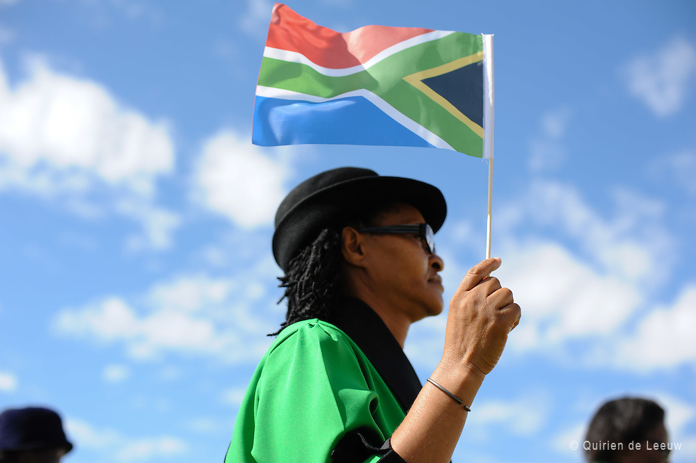 Vrouw met Zuid Afrikaanse rainbow nation vlag tijdens Freedom Day in township New Brighton, Zuid Afrika