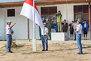 Standing on a platform, Ibu Ratna leads the flag ceremony at her school.