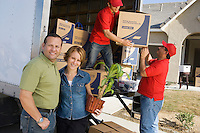 Portrait of couple and workers unloading truck