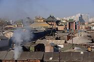 Mongolia. Ulaanbaatar. yurts area around Gandan monastery OulanBator    / Quartier de yourtes à OULAN BATOR. autour du monastere de Gandan / La capitale s'élève dans une vallée du massif du KENTI. Un couple regagne leur domicile en banlieue, dans un des quartiers de yourtes délimités par de hautes palissades en bois. Au second plan se dresse le centre ville avec ses bâtiments administratifs et immeubles d'habitation en béton. (Partie Nord-Ouest de OULAN BATOR  / 3    L921009c  /  P0002739