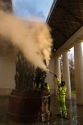 The early morning sunshine catches the rising steam as specialist clean-up workers use high pressure steam to clean the paint vandals squirted over the Bomber Command Memorial in Green Park in the early hours of Monday 21 January. The operation is expected to take at least a day. London, January 22 2019.