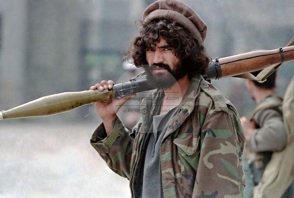 An Afghan mujahideen fighter with Jamayat-E-Islami carries a shoulder fired Rocket-propelled grenade during fighting against Hezb-i Islami forces following the fall of the capital April 19, 1992 in Kabul, Afghanistan. Fighting between mujahideen factions began almost immediately after they captured the city.