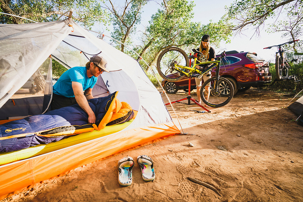 Dane Cronin sets up camp while Jeremy Hottinger wrenches on his bike, Virgin, Utah.