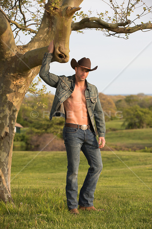 Hot muscle cowboy without a shirt holding a tree in a field