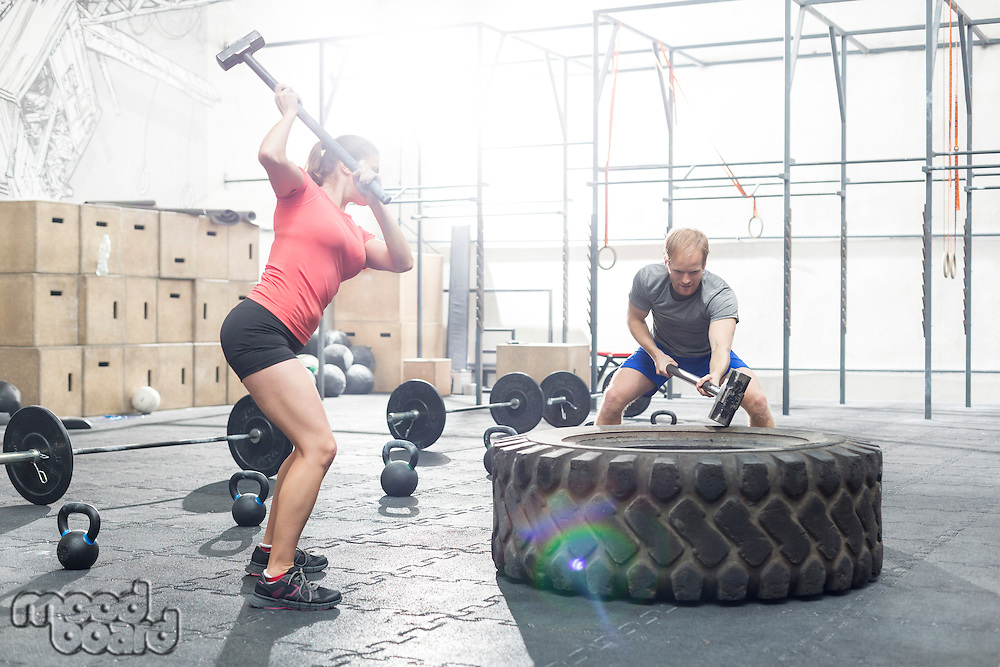 Dedicated man and woman hitting tire with sledgehammer in crossfit gym