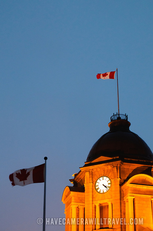 An illuminated tower of an old building in Quebec City's Old Town at dusk, with Canadian flag.