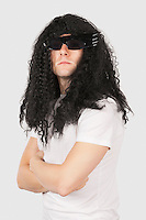 Portrait of confident young man with wig and sunglasses against gray background