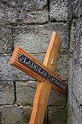 Discarded cross with a deceased person's name lying in a communal cemetery bin of a rural village in the Kozjansko Regional Park, on 24th June 2018, in Prevorje, Slovenia.
