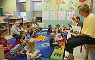 """Pearson's Kerry Wegman (second on right) reads """"Otis"""" by Loren Long as Dale Hughes (third on right) and Teresa Flack (right) hold up books to show the pictures during Jumpstart's Read for the Record event at Waypoint Uptown Kids Child Development Center in Cedar Rapids on Thursday, October 3, 2013. Jumpstart's Read for the Record in partnership with the Pearson Foundation is a world-record-breaking campaign that brings together children and adults to read the same book on the same day. 73 Pearson employees from their Iowa City location visited 34 schools and daycares in Cedar Rapids, Iowa City, and the surrounding area as part of the program."""