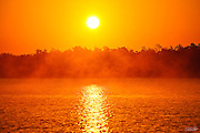 An early morning sea mist is lit by the rising sun over Plate Creek Bay as the waters in the Florida  Everglades reflect the orange dawn sky.