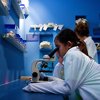 NAPLES, FL -- March 13, 2010 -- Bethany Latham, 9, of Bethlehem, Pennsylvania, looks through a microscope in the lab at leaves she collected during the Nature's Wonders program at The Ritz-Carlton in Naples, Fla., on Saturday, March 13, 2010.  The three hour programs let kids experience a more involved, educational nature program while parents get free time to enjoy themselves sans kids.