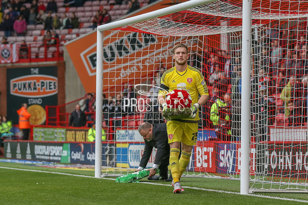 Sheffield United goalkeeper George Long picks up the flowers after a Minutes applause for Alan Hodgkinson and Martyn Harrison during the Sky Bet League 1 match between Sheffield Utd and Coventry City at Bramall Lane, Sheffield, England on 13 December 2015. Photo by Simon Davies.