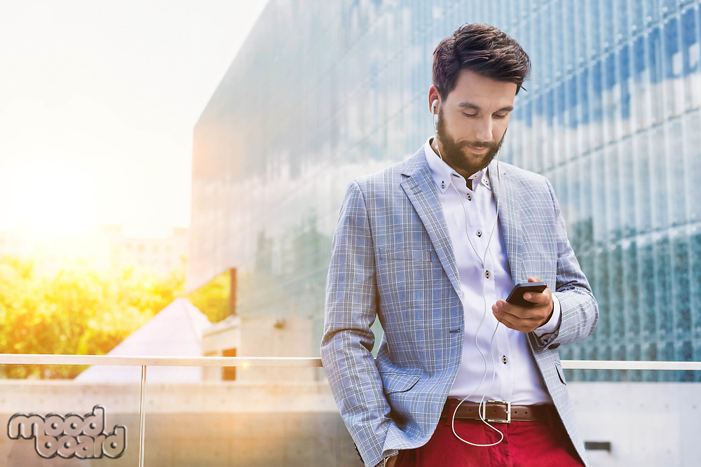 Portrait of young attractive businessman using smartphone with earphones on