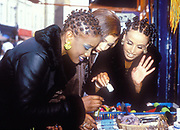 Three ladies picking out different colours of nail polish in a shop, U.K.