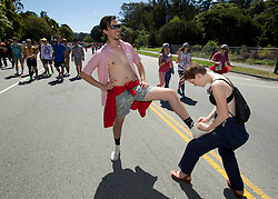 A man gets his wardrobe malfunction -- an untied shoelace -- tended to by his girlfriend while passing through Golden Gate Park, during the 105th running of the Bay to Breakers 12k, Sunday, May 15, 2016 in San Francisco. The 7.42-mile race from San Francisco Bay to the Pacific Ocean, which attracts a field of tens of thousands of runners, from elite runners to weekend warriors, some clad in costume and some in nothing at all. (Photo by D. Ross Cameron)