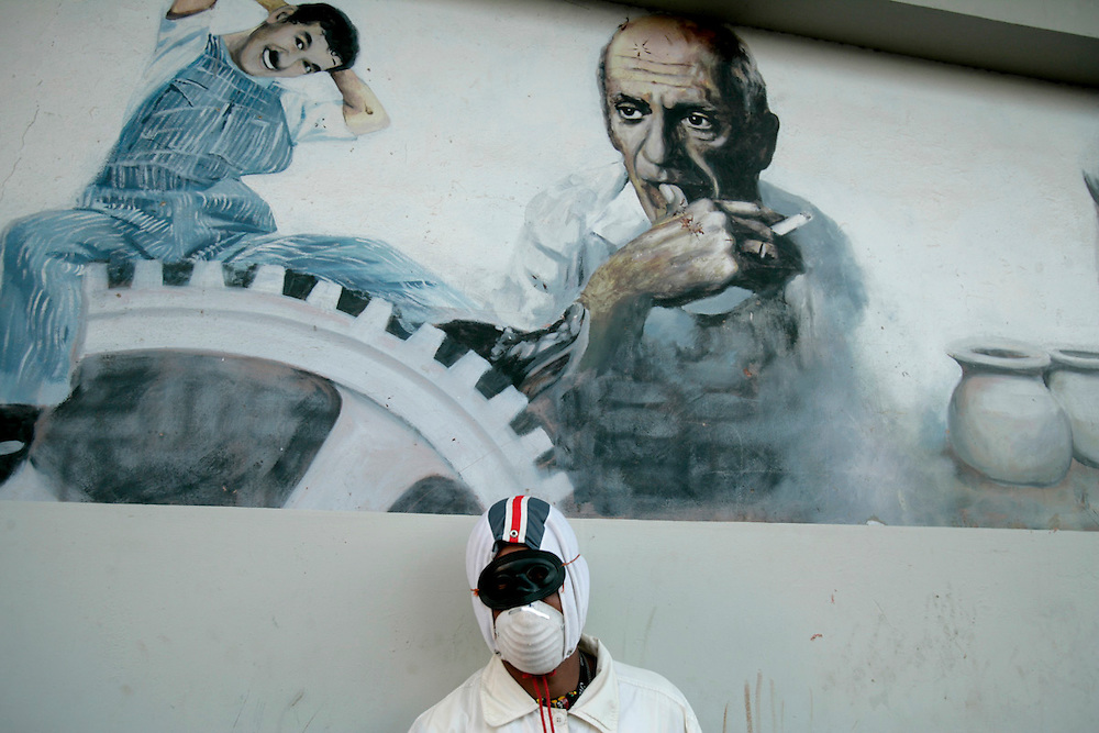 A young man with a mask in front of a street mural depicting Charlie Chaplin and Picasso during Carnival in Mindelo, the capital city of Sao Vicente island.