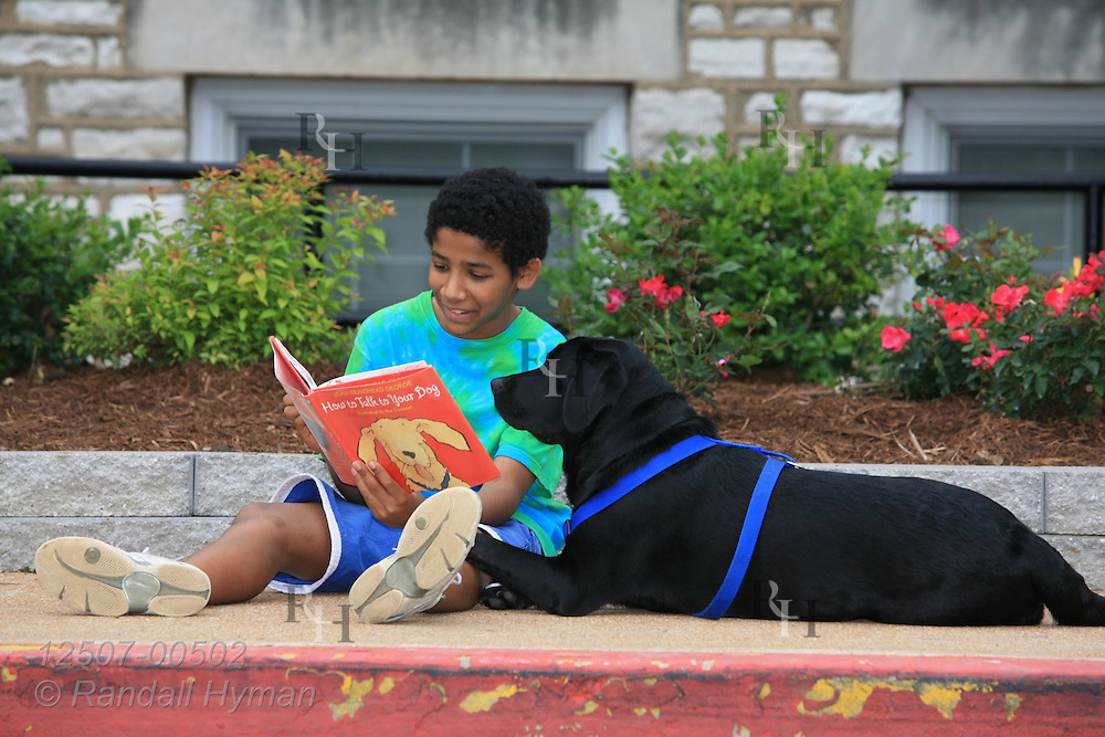 Fifth-grade African American boy reads How to Talk to Your Dog book to black lab; Kirkwood, Missouri