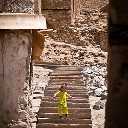 A young girl runs down stairs in Leh.