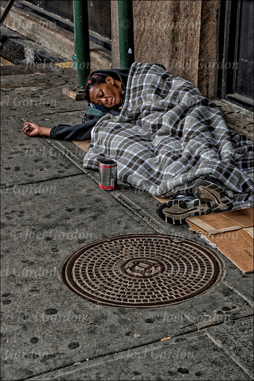 African American homeless female street person  a sleep on the street in New York City. <br /> <br /> Persons with serious and persistent mental health problems may be forced to live on the streets in precarious circumstances.