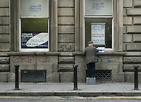Man standing on box cleaning the outside windows of a letting agency office in Dublin Ireland