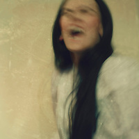A black haired lady in a white dress with deformed face sitting in front of a Wall and screaming