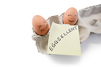 Smiley faces on eggs with 'eggsellent' written on notepaper