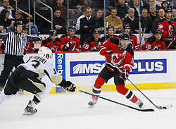 Dec 10, 2008; Newark, NJ, USA; New Jersey Devils center John Madden (11) takes a shot while being defended by Pittsburgh Penguins defenseman Alex Goligoski (13) during the second period at the Prudential Center.