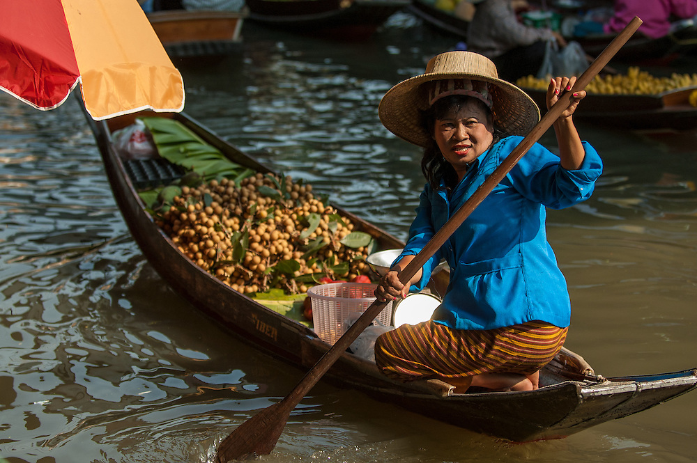 Woman selling fruit from her canoe at the Floating Market in Damnoensaduak, Thailand. She is a villager selling her wares from a canoe or row boat in the canals west of Bangkok.