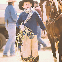 young cowboy with horse rope in hand