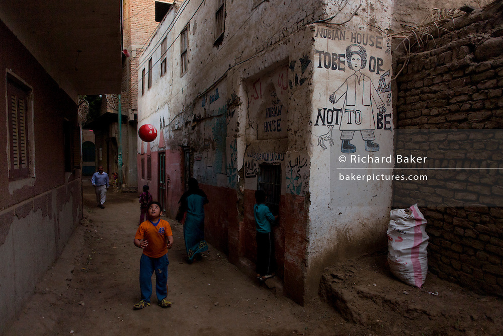 A young Egyptian plays football near a Shakepearean quote, written on the wall of a house in the village of Bairat on the West Bank of Luxor, Nile Valley, Egypt.