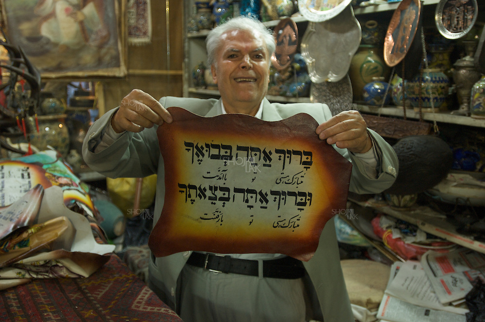 Iran, Tehran, April 2008, Famous Jewish Antique dealer Moses BABA showing Hebrew hand righting on piece of Leather in his shop.