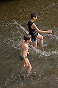 two kids playing in a stream