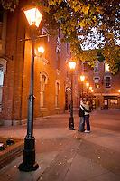 Old style Streetlights create a romantic air for an embracing couple in Bastion Square.  Victoria, Vancouver Island, British Columbia, Canada.