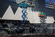 Workmen fix triangular-shaped cladding to the exterior of a part of the One Blackfriars residential tower, on 27th October 2017, in Southwark, London, England. 1 Blackfriars or One Blackfriars, is a mixed-use development at the junction of Blackfriars Road and Stamford Street at Bankside, London. The development is a 52-storey 170m tower and two smaller buildings of 6 and 4 stories respectively. Uses include residential flats, a hotel and retail.