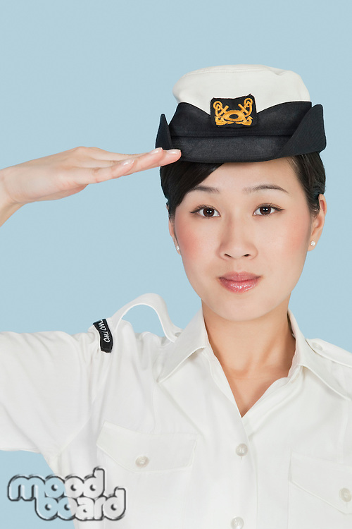 Portrait of a beautiful young US Navy officer saluting over light blue background