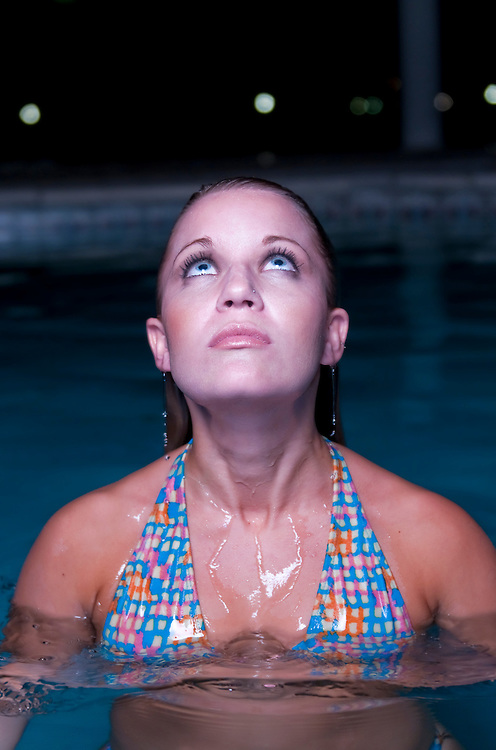 Young woman emerging from a swimming pool in resort hotel at night.