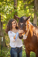 A beautifu lyoung woman lovingly caresses her horse while she smiles for the camera.  She is wearing jeans and and a white bohemian style blouse.