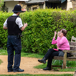 © Licensed to London News Pictures. 08/04/2020. London, UK. A policeman speaks to a women sitting on a bench at Barnes Pond. Police out in upmarket Barnes Village asking locals not to loiter in the warm weather with their lattes and picnics as Good Friday is set to be the warmest day of the year so far as the Coronavirus crisis continues. Photo credit: Alex Lentati/LNP