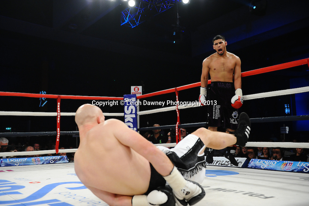 Arfan Iqbal (black shorts) knocks down Leon Senior during a Light Heavyweight contest. Glow, Bluewater, Kent, UK. Hennessy Sports © Leigh Dawney Photography 2013.