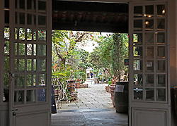 Entry into a courtyard lined with 30 antique shops.  Known for its twice a week markets and numerous antique and design shops, L'Isle-sur-la-Sorgue draws visitors touring Provence in Southern France. This entrance leads to a courtyard lined with antiques and shopping.