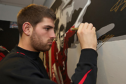 SWANSEA, WALES - Monday, March 1, 2010: Wales' Ched Evans autographs a painting before training at the Liberty Stadium ahead of the international friendly match against Sweden. (Photo by David Rawcliffe/Propaganda)