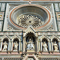 Duomo Upper Central Section Facade Close Up in Florence, Italy <br /> Some Duomo critics protest that it is over decorated.  However, I was mesmerized by all the intricate features on this Roman Catholic basilica and thankfully a long lens brought them up close for inspection.  An example is this huge, gorgeous rose window.  Below it is a statue of Mary with the infant Jesus.  In fact, the entire façade is dedicated to the Mother of Christ.