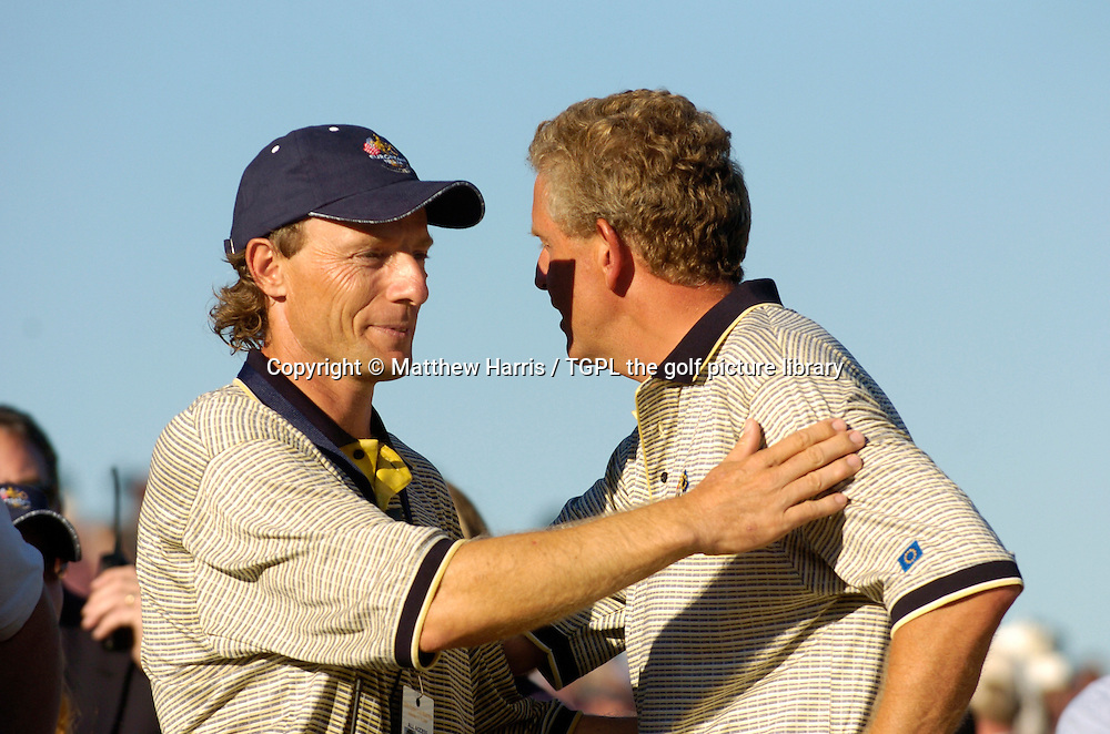 Winning captain Bernhard LANGER (EUR) celebrates a sweet victory over team USA 18.5 points to 9.5 by congratulating Colin MONTGOMERIE (EUR) winning his against David TOMS (USA) at 18th during final day Singles of the Ryder Cup Matches 2004,Oakland Hills (South Course),Bloomfield,Michigan,USA.