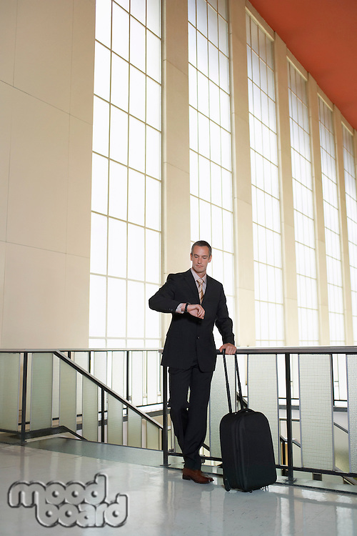 Business man checking watch in airport lobby